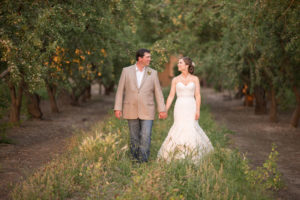 newly married couple walking through the orange groves